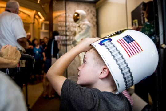 Jack Heely, 5, of Alexandria, Va., wears a toy space helmet as he arrives as one of the first visitors to view Neil Armstrong's Apollo 11 spacesuit, background, after it is unveiled at the Smithsonian's National Air and Space Museum on the National Mall in Washington, Tuesday, July 16, 2019.