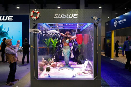 "In this Jan. 9, 2019, file photo a woman dressed as a mermaid performs at the Sublue booth at CES International in Las Vegas. The group that organizes the annual CES gadget show is cracking down on its dress code, introducing more programming focused on women and minorities and creating a new ""sex tech"" category. The moves are aimed at addressing complaints that the 52-year-old electronics show is too male-dominated."