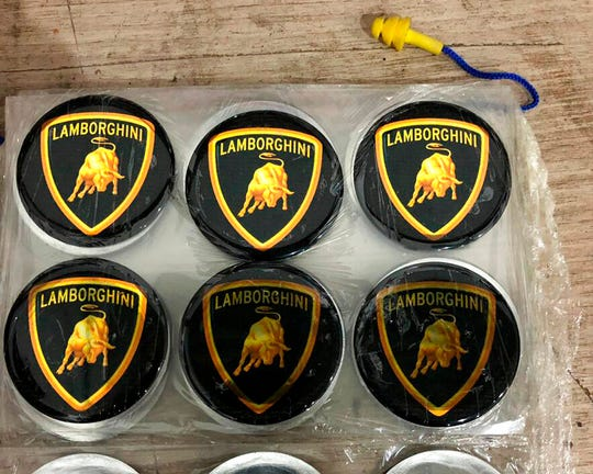 This July 15, 2019 photo released by Itajai Civil Police shows emblem badges stamped with the Lamborghini logo, inside a workshop in Itajai, Brazil.