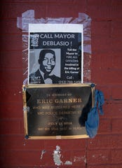 A sign and plaque are mounted on a wall at the sidewalk area where Eric Garner was apprehended by police in the Staten Island borough of New York, Tuesday, July 16, 2019.