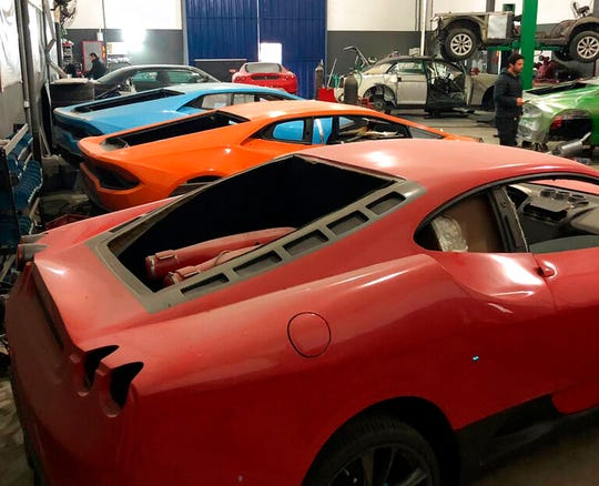 This July 15, 2019 photo released by Itajai Civil Police shows luxury car replicas inside a workshop in Itajai, Brazil.