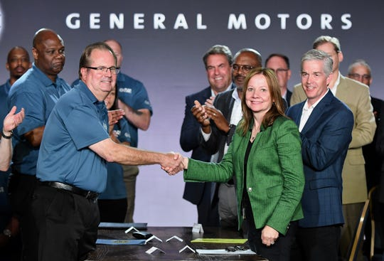 UAW President Gary Jones and General Motors CEO Mary Barra shake hands as labor contract talks with the automaker officially opened  Tuesday in Detroit.