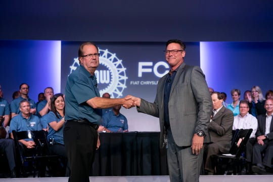 Gary Jones, president of the UAW, left, and Mark Stewart,  chief operating officer for Fiat Chrysler in North America, exchanged the ceremonial handshake marking the beginning of contract negotiations Tuesday in Auburn Hills.
