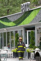 A Detroit fire fighter monitors the situation outside the evacuated Parc restaurant after a fire was extinguished at the Campus Martius Park eatery in downtown Detroit Tuesday afternoon, July 16, 2019.