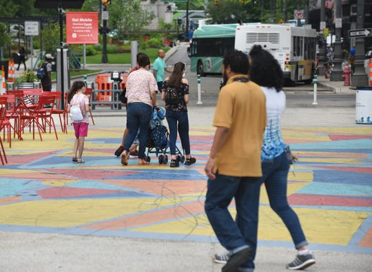 People walk through Spirit Plaza Tuesday with its colorful painted geometric shapes on the northbound lane of Woodward  between Jefferson and Larned.