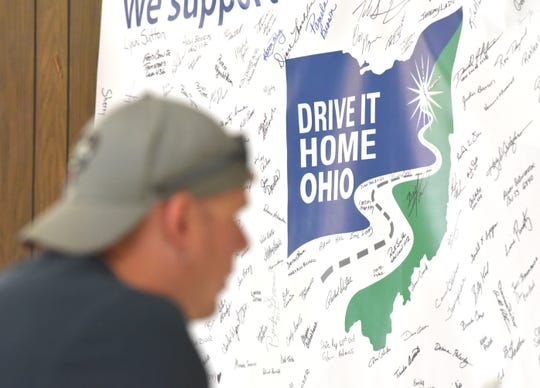 Layed off UAW Lordstown worker Craig Lynn, of Youngstown, talks to a trades representative about continuing education in front of a Drive It Home Ohio community support banner with citizens' signatures supporting layed-off UAW workers.