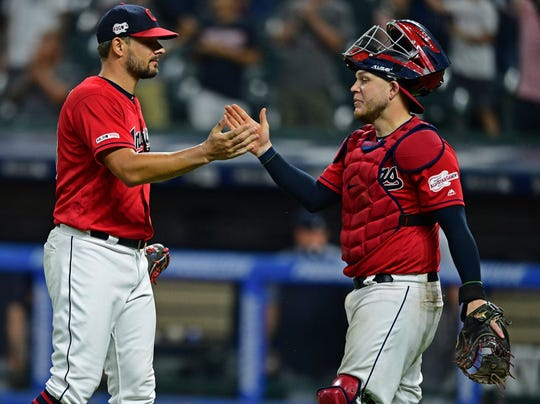 Cleveland Indians relief pitcher Brad Hand, left, is congratulated by catcher Roberto Perez after defeating the Detroit Tigers Monday night.