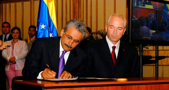 In this June 26, 2007 file photo, then Chevron's top executive for Latin America Ali Moshiri signs a deal with Venezuela's state oil company Petroleos de Venezuela SA (PDVSA), as Venezuela's Energy Minister Rafael Ramirez watches, at PDVSA headquarters in Caracas, Venezuela. In 2007, as rivals Exxon and Conoco fled the country and sued amid a nationalization drive, Chevron rode alone in taking up Hugo Chavez's offer to form a joint venture with PDVSA on what were widely seen as unfavorable terms.
