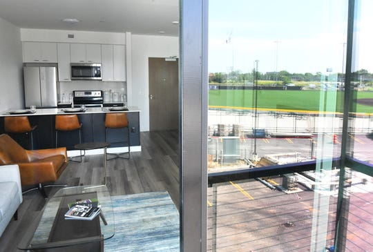 This is the interior of a one bedroom unit, with The Corner Ballpark reflected in the sliding glass doors.