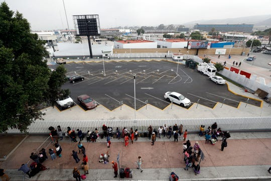 Migrants line up along an entrance to the border crossing as they wait to apply for asylum in the United States, Tuesday, July 16, 2019, in Tijuana, Mexico.