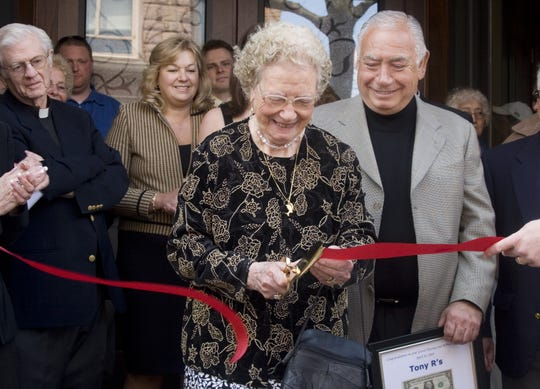 Grace Ruggiero cuts the ribbon Wednesday in front of Tony R's as her son Tony Ruggiero, right, and his wife Maurina Ruggiero, left, look on as they celebrate the opening of the upscale restaurant on Market Street in Corning.