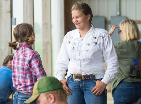 Dora Green, middle, laughs with her friend Georgia Fletcher, left, during the Warrick County 4-H Fair Horse Performance Classes Tuesday, July 16, 2019.