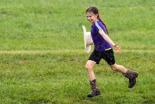 Alayna Horn, 8, runs through the rain with her cowgirl hat while a storm temporarily pauses the Warrick 4-H Fair Horse Performance Classes Tuesday, July 16, 2019.