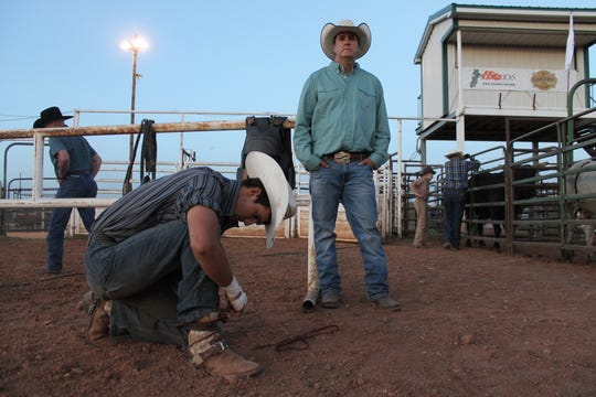 Jaren Sturgis, left, gets ready before the Laramie Jubilee Days junior bull riding competition July 10, 2019, as his father, Jeremy, stands nearby.