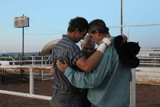 Jaren Sturgis, left, John Tillotson, middle, and Jeremy Sturgis pray together before the Laramie Jubilee Days junior bull riding competition July 10, 2019. Tillotson taught both generations of Sturgis men how to ride bulls.