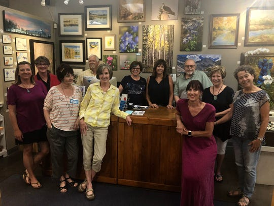 Fort Collins Blue Moose Art Gallery owners and artists pose in the gallery.