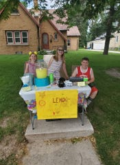 Addison (left), Kaylen (middle) and Aidan (right), are ready for customers at their lemonade stand. A replica of Zoey the police dog sits center above the homemade sign.
