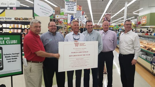 On July 10, the Wisconsin Grocers Association surprised former Festival Foods executive Marlin Greenfield with the Grocer of the Year Award for 2019. Pictured, from left, are Wisconsin Grocers Association CEO Brandon Scholz, Russ Davis Wholesale's Mark Maloney, Greenfield, and Festival executives Darrin Kuehn, Mark Gayhart and Steve Burkhardt.