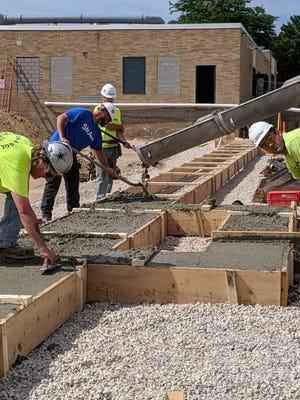 Workers from Peters Concrete Co. of Green Bay pour concrete for the wall footing for the new gymnasium at Luxemburg-Casco High School.
