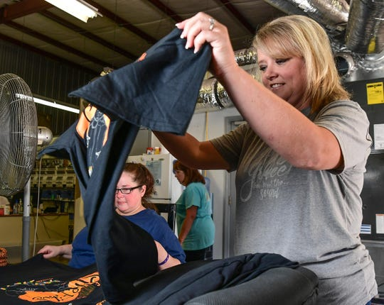 Angel Rice, owner of Under the Carolina Moon in Easley, looks over one of the T-shirts in the fall collection while, and talks about giving back to the community Tuesday. The store is moving to a new location inside the city limits of Easley.