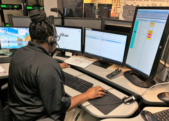 A Greenville dispatcher monitors calls at her work station.