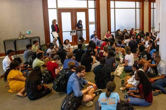 USC students sit inside the alumni center as they protest University of South Carolina's presidential finalist Robert L. Caslen, former superintendent of West Point, Friday April 26, 2019, in Columbia, S.C.