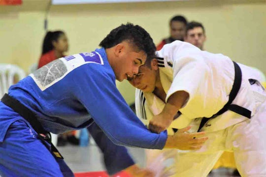 Joshter Andrew, left, fights against a New Caledonia judoka at the Pacific Games July 16 in Samoa. His opponent gave up, sending Andrew to the gold medal match.
