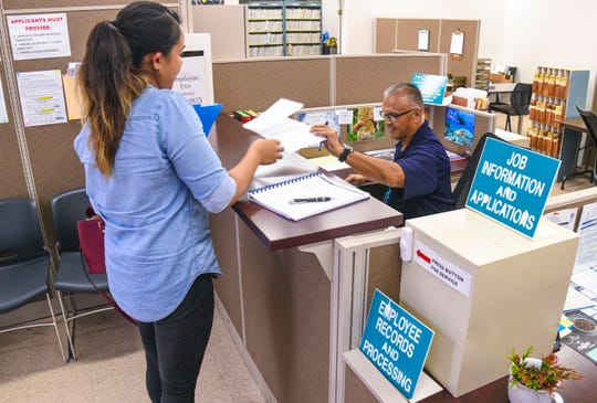 Personnel specialist Anthony Cepeda, right, receives supplemental documentation from a employment applicant at the Department of Administration Human Resources Division in Tamuning on Tuesday, July 16, 2019.