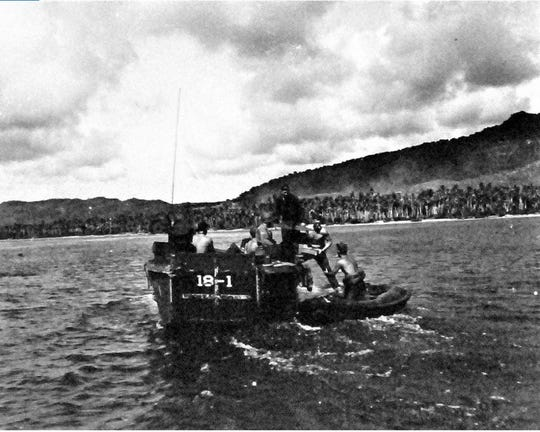 An underwater demolition team transfers an explosive from Higgins boat to rubber boat to be planted in the coral heads and cribs along the beach days before the invasion of Guam.
