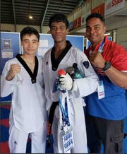 Joseph Ho, left, won a bronze medal in taekwondo and Alexander Allen won a silver after fighting in the gold medal match against Australia July 16 in the Pacific Games. Shown at right is coach Ron Cook.