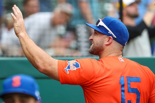 Syracuse Mets outfielder Tim Tebow, a former NFL quarterback, waves to fans from the dugout at Victory Field on Monday, July 15, 2019.