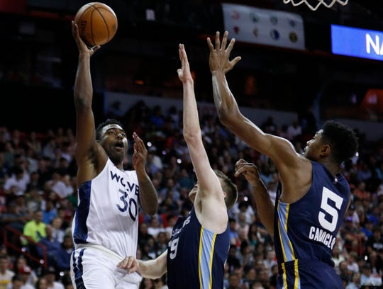 Minnesota Timberwolves' Kelan Martin, left, shoots around Memphis Grizzlies' Peyton Aldridge, center, and Bruno Caboclo during the first half of an NBA summer league basketball game Monday, July 15, 2019, in Las Vegas.