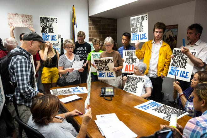 Maureen Vasile, of Iowa City, reads from a sheet of paper while members of the Catholic Worker House gather for a conference call with a staffer from the office of U.S. Rep. Dave Loebsack in Washington, D.C., Tuesday, July 16, 2019, at Loebsack's office in downtown Iowa City, Iowa.