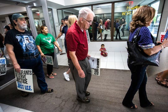 Members of the Catholic Worker House walk out to a bus after gathering for a conference call with a staffer from the office of U.S. Rep. Dave Loebsack, Tuesday, July 16, 2019, at Loebsack's office in downtown Iowa City, Iowa.