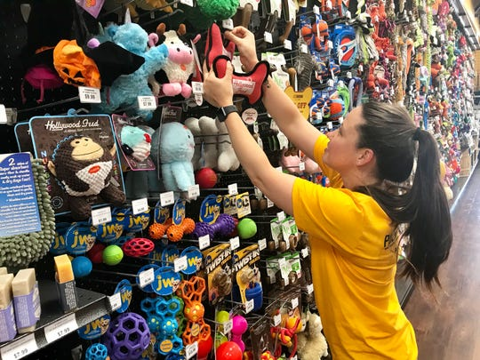 Jessica Thomasson of Madison, manager of Hollywood Feed in Madison, adds additional merchandise to a wall of pet toys at the store.