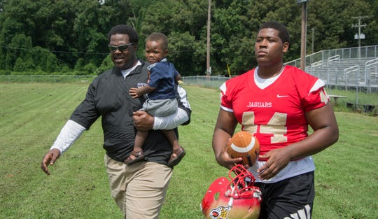 Montra Edwards Jr., of Lexington, walking with his father Montra Edwards Sr., is a 6-3, 290-pound, strong-side defensive tackle at Holmes County Central High.
