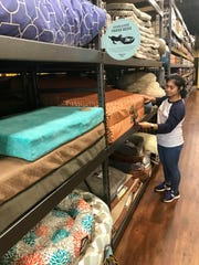 Julianne Ranis of Brandon, third key at Hollywood Feed in Madison, straightens dog beds.