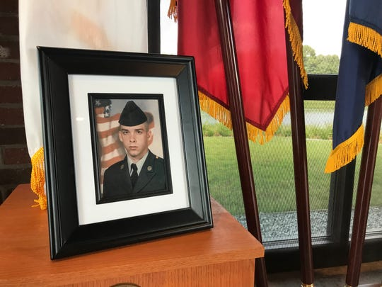 A photograph of veteran Jessie Thurston during his time in service rests on a table backed by U.S. military flags at his memorial service at the Tennessee State Veteran's Cemetery at Parkers Crossroads on July 12, 2019.
