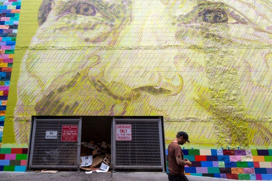 Seattle-based artist Addison Karl walks past the completed portrait of one of the six East Tennesseans being featured on the large mural he is painting in an alleyway on a wall of the Market Square Garage on Monday, July 15, 2019.