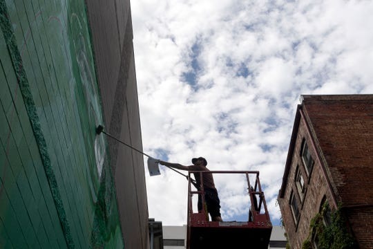 Artist Addison Karl continues work on the mural he is creating for a wall of the Market Square Garage on Monday, July 15, 2019. The mural takes up most of the length of the garage in the alleyway between Wall and Union avenues.