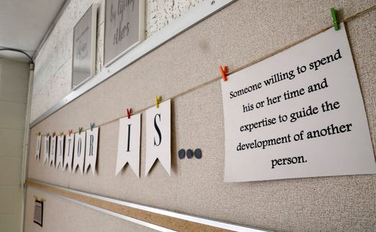 A sign hanging in a group space used for mentorship gives a definition of a mentor. The space is used by the Fairfield County Juvenile Court to do group mentoring programs with children involved with the court.