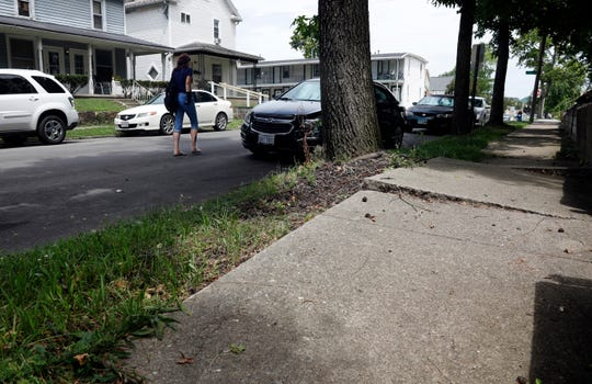 A woman walks along of the side of Harrison Avenue past a section of uneven sidewalk Tuesday afternoon, July 16, 2019, in Lancaster. Mayor David Scheffler wants to use some of the money from a proposed income tax levy that's currently before the city council to help property owners repair sidewalks damaged by some trees.