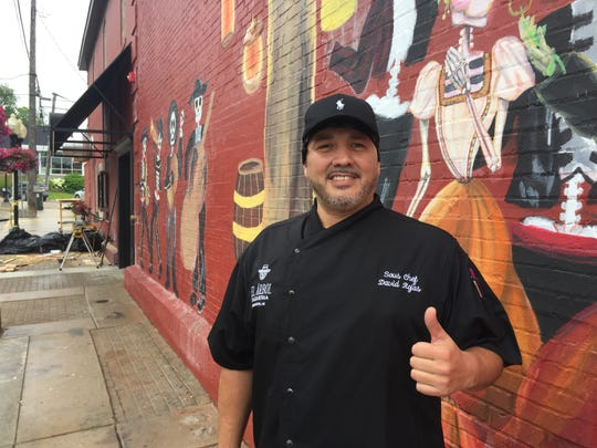 El Àrbol sous chef David Rojas stands near a mural painted on the side of the new Brighton restaurant, Tuesday, July 16, 2019.