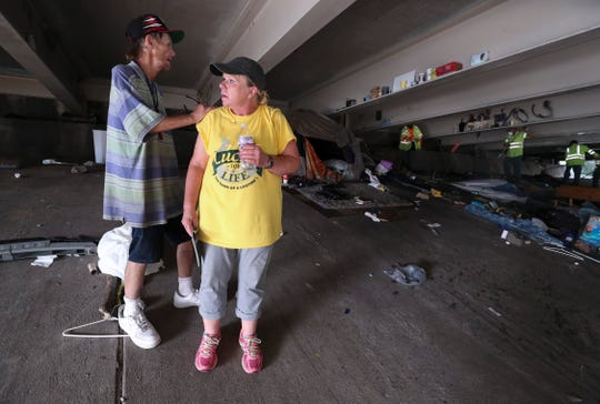 Brent Spradlin, left, placed his hand on his friend Kim Morrow's shoulder as they watched city crews clear out the remnants of a homeless camp beneath the I-65 overpass at Brook and Breckinridge streets where they lived in tents next to each other.   July 16, 2019