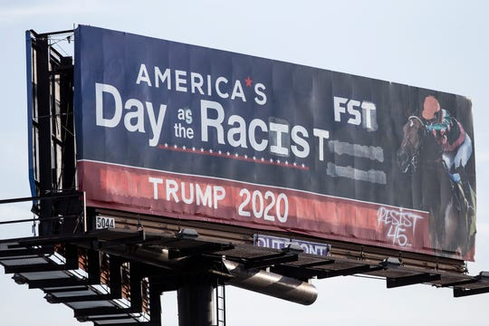 "A billboard on northbound I-65 near the Kentucky Expo Center was manipulated by the graffiti artist ""Resist45"" to call President Trump a racist. July 16, 2019"