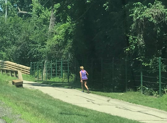 A woman runs the Lansing River Trail Monday, July 15, 2019 by the Red Cedar Natural Area where a man who was impaled on a stump after a fall from a tree was rescued Saturday.