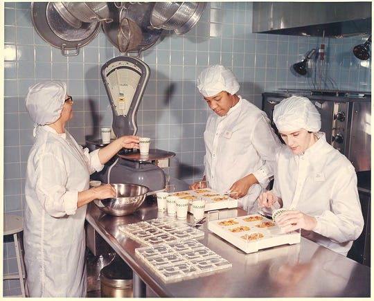 Workers test food to go with Whirlpool's Space Kitchen, developed in a contract with the Air Force to be used by astronauts.