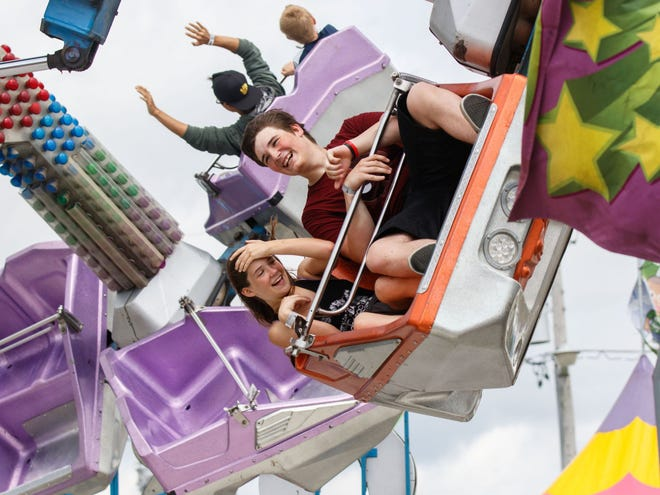 Akira Cooper, 13, and her brother Jerrick, 15, of West Allis, enjoy a carnival ride at the Waukesha County Fair in 2017.