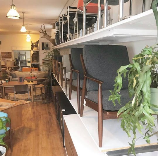 Mid-century chairs are lined up on shelves at Brew City Salvage.