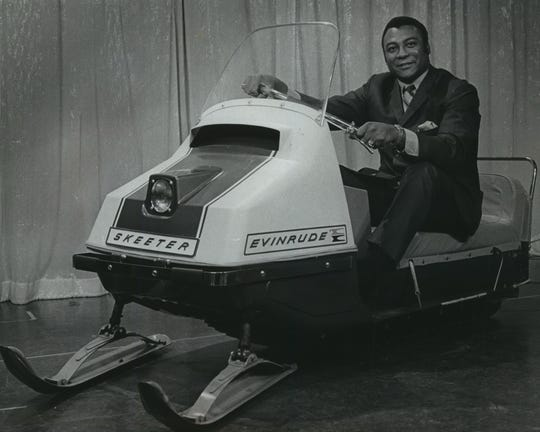 Green Bay defensive end and WTMJ-TV sportscaster Lionel Aldridge poses with an Evinrude Skeeter snowmobile, one of the prime attractions at the first TV auction held by Milwaukee's public televisions in the spring of 1969. This photo was published in the March 16, 1969, Milwaukee Journal.